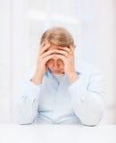 Vieil homme soumis à une contrainte tenant la tête à la maison Photos stock
