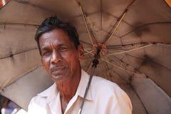 Vieil homme sous un parapluie Image stock