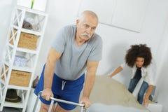 Vieil homme supérieur avec le marcheur dans la maison de repos Image stock