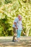 Vieil homme sur des béquilles avec une femme Photo stock