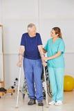 Vieil homme sur des béquilles en physiothérapie Photos stock
