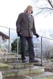 Vieil homme sur des béquilles sur les escaliers glacials en hiver Photographie stock