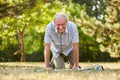 Vieil homme sur des béquilles sur ses genoux Image libre de droits
