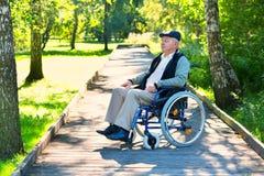 Vieil homme sur le fauteuil roulant en parc Photographie stock libre de droits