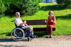 Vieil homme sur le fauteuil roulant et la jeune femme sur un banc Photos libres de droits