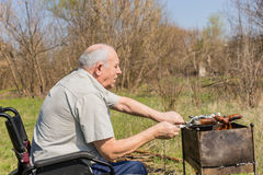 Vieil homme sur le fauteuil roulant grillant des extérieurs de saucisse Image libre de droits