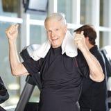 Vieil homme sur le tapis roulant au centre de fitness Photos libres de droits
