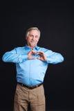 Vieil homme tenant des mains dans la forme du coeur Photo libre de droits