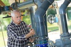 Vieil homme travaillant à la section de tuyau de PVC de l'eau Photo stock