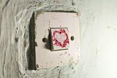Vieil interrupteur de lampe avec le coeur rouge de peinture sur le vieux mur vert criqué Photo libre de droits