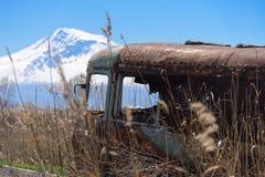 Vieil l'autobus russe soviétique abandonné et rouillé au milieu des roseaux et de l'agriculture met en place avec le Mt Ararat su Photographie stock