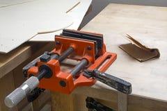 Vieil étau de table dans l'orange avec la poussière et rouille sur un établi à la maison Photographie stock libre de droits