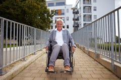 Vieil utilisateur de fauteuil roulant sur le rampe Photographie stock libre de droits