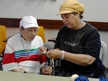 Vieillard apprenant à faire du crochet Image libre de droits