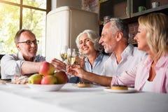 Vieillard ayant la fête d'anniversaire encourageant avec du vin Photos stock