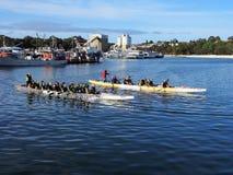 Vieillards barbotant de longs canoës Photo stock