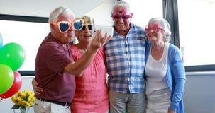 Vieillards prenant le selfie au téléphone portable pendant la fête d'anniversaire clips vidéos