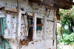 Vieille échelle accrochant sur un entrepôt blanc dans un village grec photographie stock