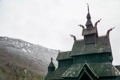 Vieille église de barre avec les barres complexes contre le ciel neigeux blanc et la montagne couverte de neige en Norvège photo libre de droits