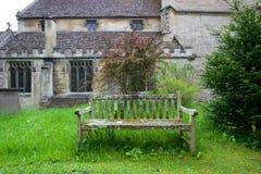 Vieille église en pierre extérieure de banc en bois Photographie stock