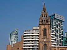Vieille église et appartements modernes élevés neufs Images stock