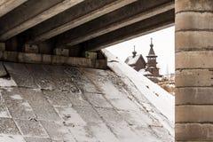 Vieille église orthodoxe en bois sous un pont Photos stock