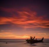 Vieille épave cassée de bateau sur le rivage, une mer congelée et le beau fond bleu de coucher du soleil Photos stock