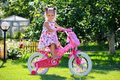 Vieille équitation de quatre ans mignonne de fille sa bicyclette Photo stock
