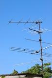 Vieille antenne de TV sur le toit de maison avec le ciel bleu Photographie stock libre de droits