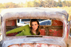 Vieille automobile rouillée avec le jeune femme à l'intérieur Photographie stock libre de droits
