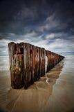 Vieille barrière de mer de bois de construction avec le ciel nuageux Photographie stock libre de droits