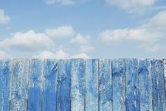 Vieille barrière en bois contre le ciel nuageux bleu Images stock