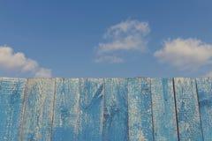 Vieille barrière en bois contre le ciel nuageux bleu Photo stock