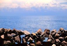 Vieille barrière en pierre avec l'eau, les nuages et le ciel bleu à l'arrière-plan photographie stock libre de droits