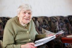 Vieille belle femme supérieure de 85 ans de livre de lecture, à l'intérieur Image libre de droits