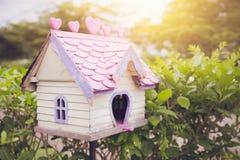 Vieille belle maison en bois d'oiseau de volière dans le jardin avec la lumière du soleil de matin Photo libre de droits