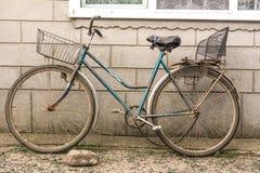 Vieille bicyclette avec un panier fait main et un siège fait main Photo stock