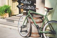 Vieille bicyclette contre le café le jour ensoleillé Images stock