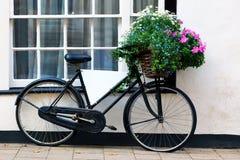 Vieille bicyclette de publicité avec le panier des fleurs Photographie stock libre de droits