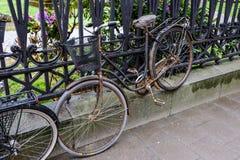 Vieille bicyclette près de la barrière d'église Photo stock
