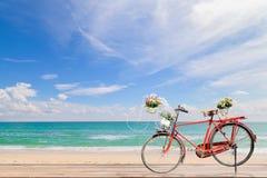 Vieille bicyclette sur le bois avec plage a de mer de turquoise la belle mer, Photos stock