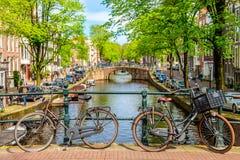 Vieille bicyclette sur le pont ? Amsterdam, Pays-Bas contre un canal pendant le jour ensoleill? d'?t? Vue iconique de carte posta image stock