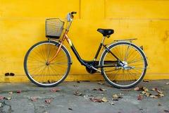 Vieille bicyclette sur un fond de mur jaune peint lumineux photos libres de droits