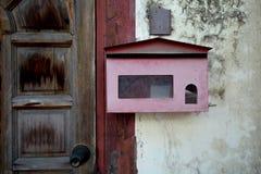Vieille boîte aux lettres rouge sur le mur Images stock