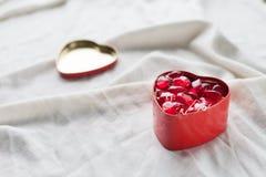 Vieille boîte dans la forme de coeur sur le fond blanc, sur le tissu blanc, dans les dragées à la gelée de sucre douces rouges de Photo libre de droits