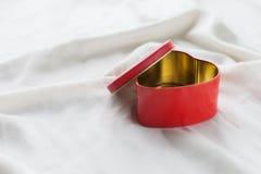 Vieille boîte dans la forme de coeur sur le fond blanc, sur le tissu blanc, dans les dragées à la gelée de sucre douces rouges de Photos libres de droits