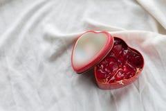Vieille boîte dans la forme de coeur sur le fond blanc, sur le tissu blanc, dans les dragées à la gelée de sucre douces rouges de Photos stock