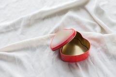 Vieille boîte dans la forme de coeur sur le fond blanc, sur le tissu blanc, dans les dragées à la gelée de sucre douces rouges de Images stock