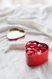 Vieille boîte dans la forme de coeur sur le fond blanc, sur le tissu blanc, dans les dragées à la gelée de sucre douces rouges de Photographie stock libre de droits