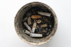 Vieille boîte de bidon avec des mégot à l'intérieur Photo sur un fond blanc photographie stock libre de droits
